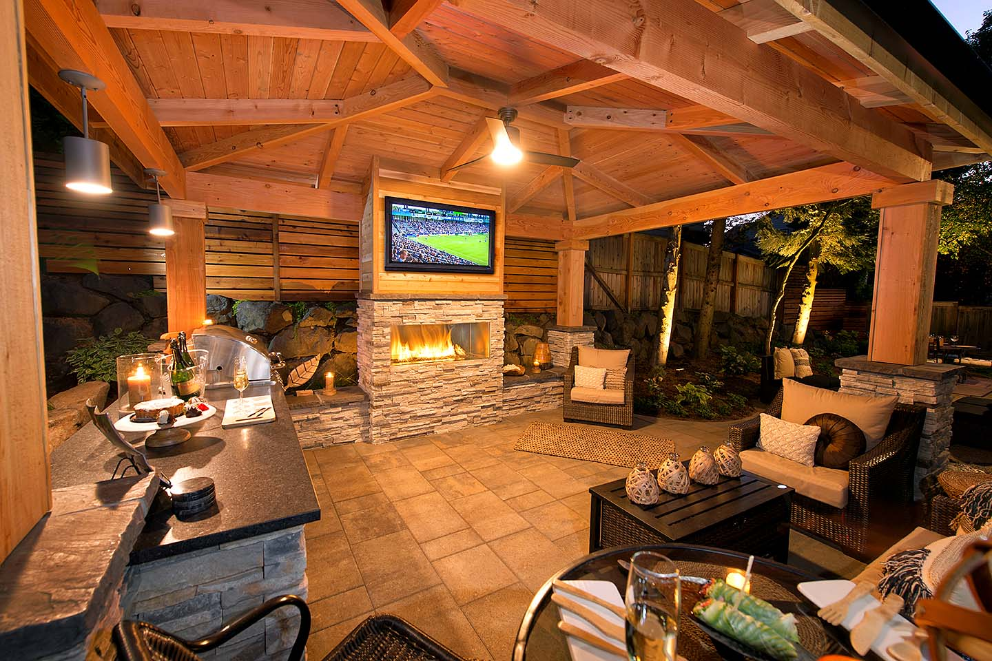 Outdoor Living Room for game night! Bar island grill and counter, gas fireplace, TV,  & seat walls - Outdoor over head lighting & pendulum lights over Bar
