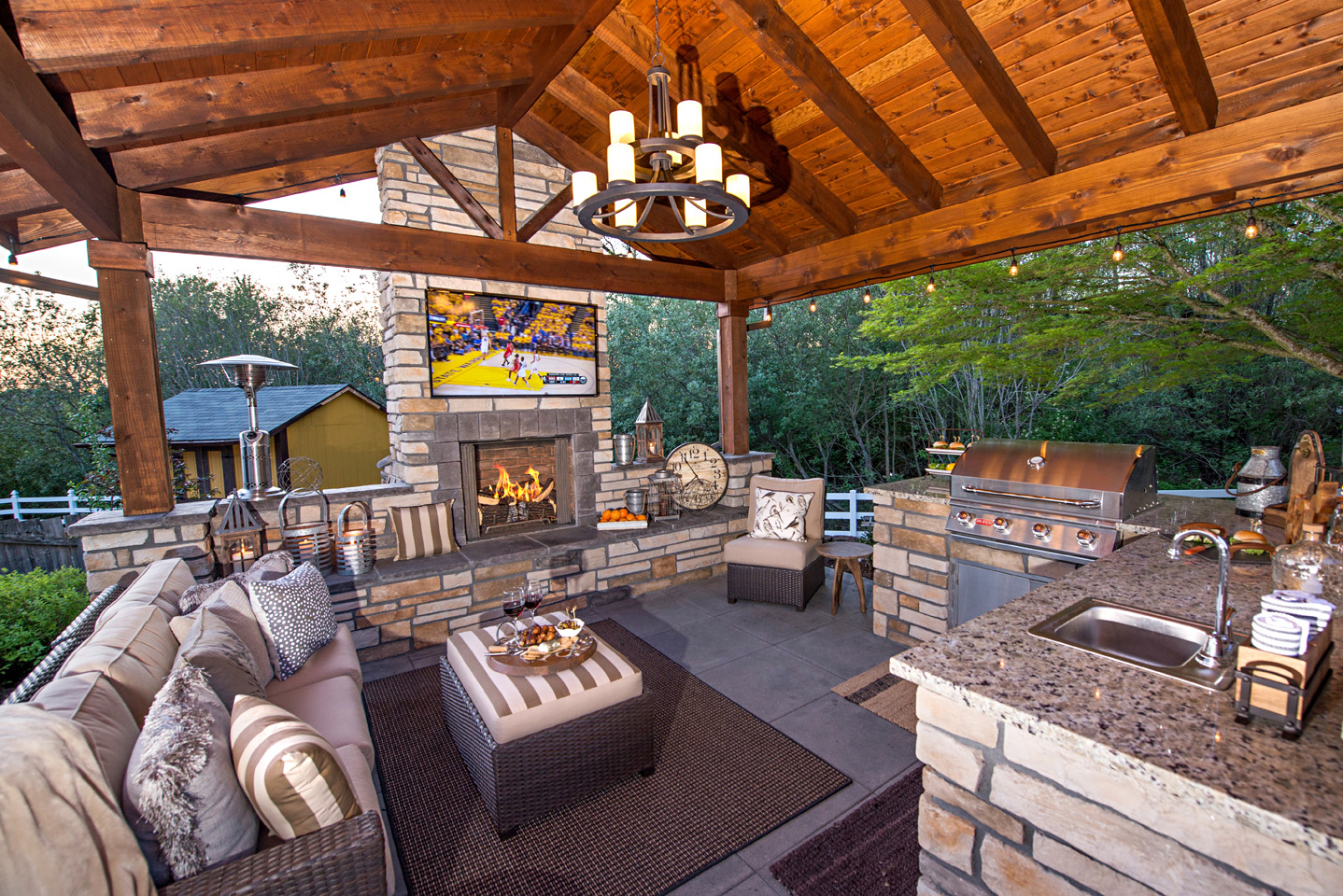 'Its Got It All' - outdoor living room with mini-kitchen, fireplace wall, TV,  grill, bar with bar stools, outdoor lighting, & the kitchen sink!