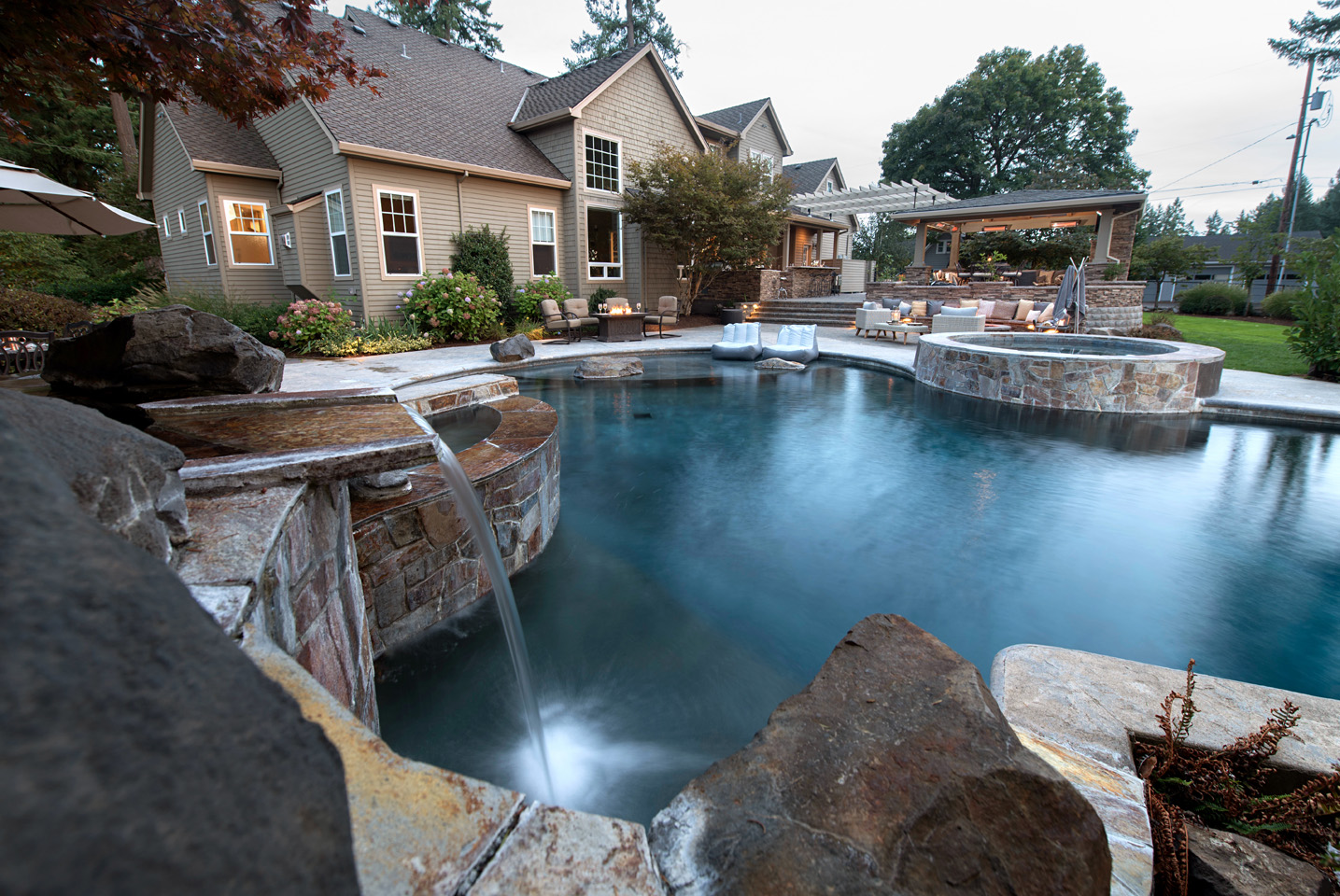 Waterfalls into pool with boulder elements add extra visual  - the pool & hot spa doubly inviting